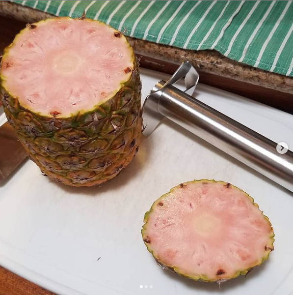 Whole pineapple with the top cut off standing on a cutting board next to a pineapple cutting gadget. The inner flesh of the pineapple is light pink.