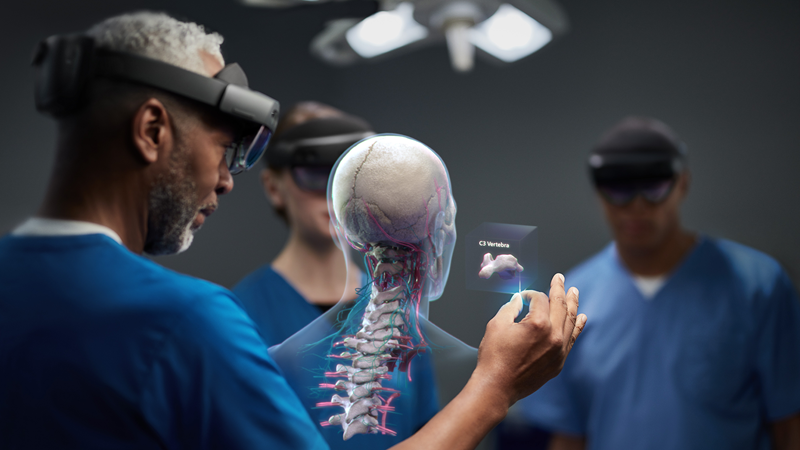 Three medical professionals all wearing HoloLens looking at a rendering of a human skeleton.