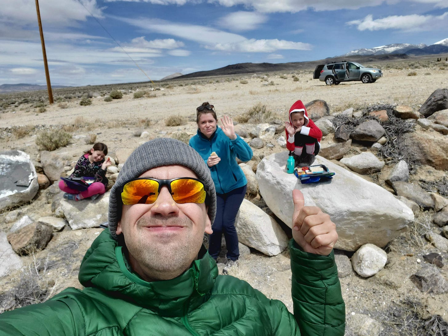 Eric taking a selfie with C, Charlotte, and L behind him sitting on rocks with their lunches in front of them.