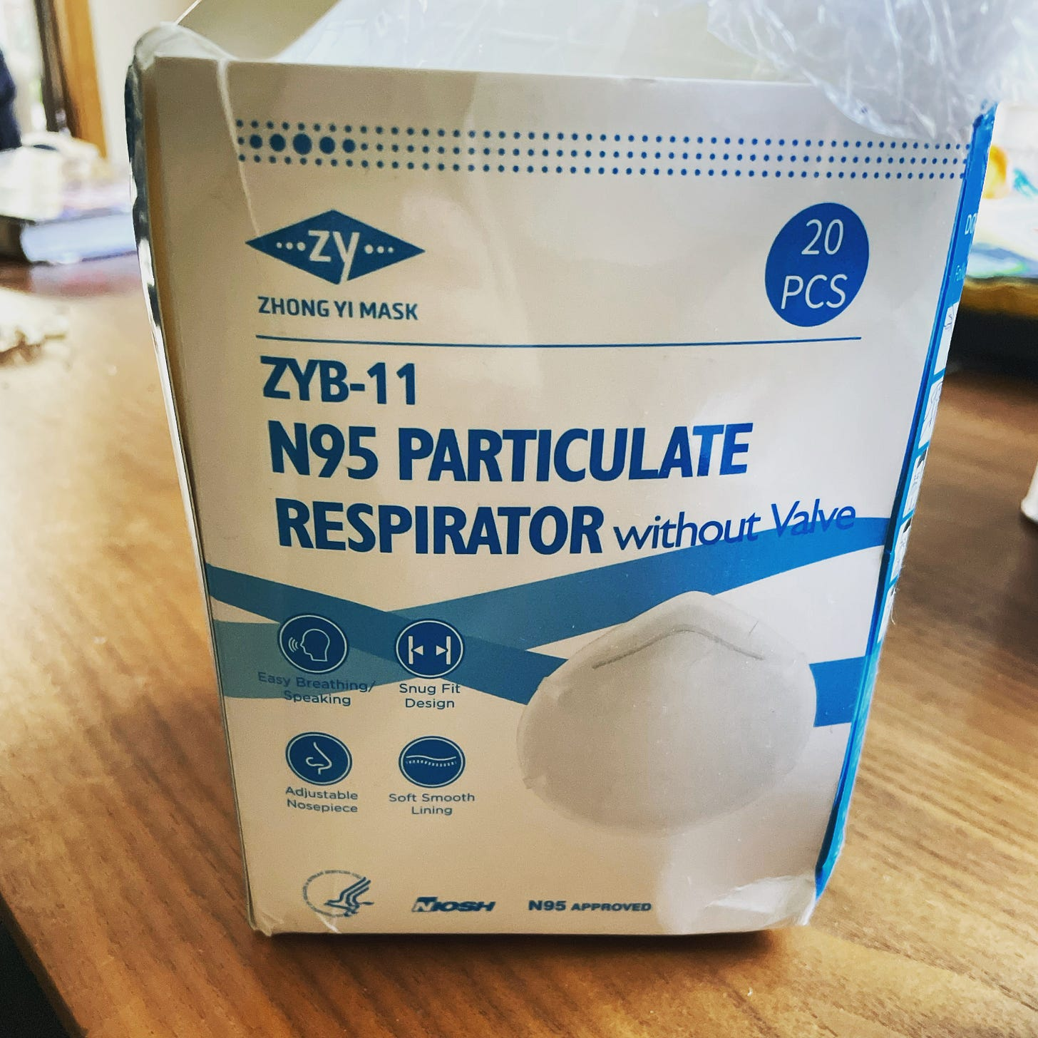"""An open and slightly distressed box of N95 masks. The blue lettering on a white box reads, in part, """"Zhong Yi Mask, ZYB-11, N95 Particulate Respirator without valve"""""""