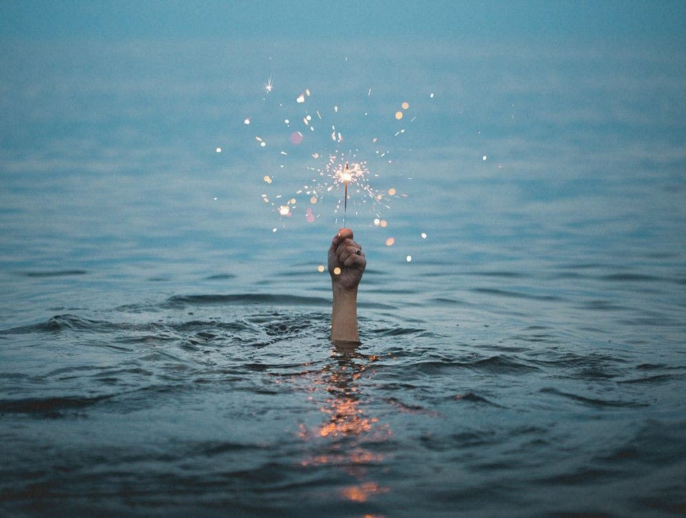 person submerged on body of water holding sparkler