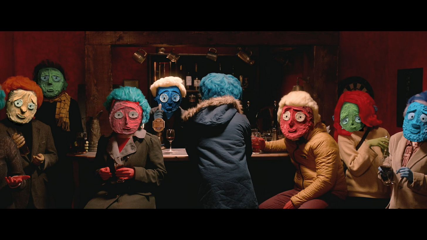 Still from the short film: A group of people with claymation faces sit at a bar staring down the camera at the viewer.