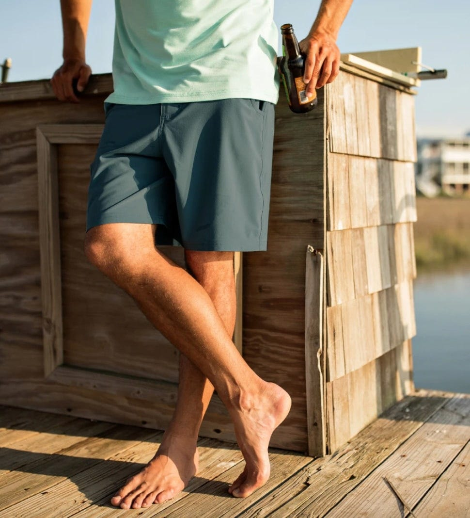 a man wearing free fly hybrid shorts leaning against a bar and having a good time