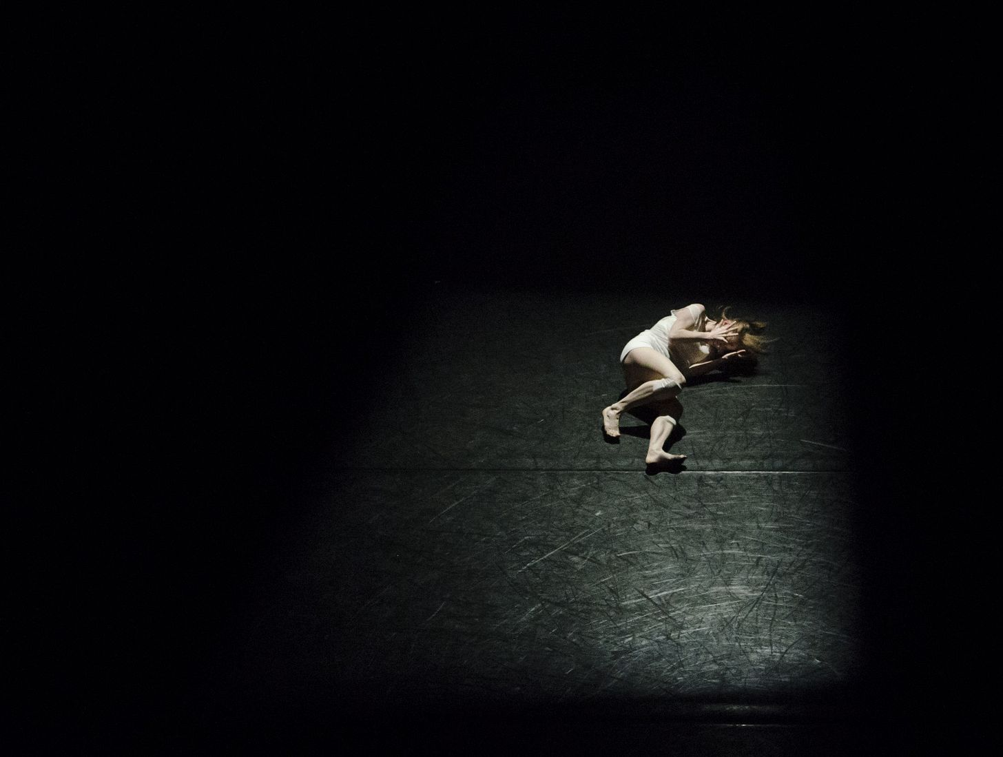 image of an actor lying on a black stage holding her head
