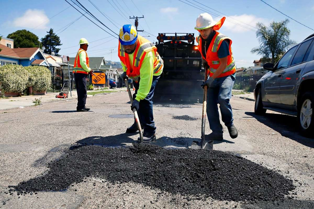 Photo of workers in orange vests filling a pothole in a residential neighborhood