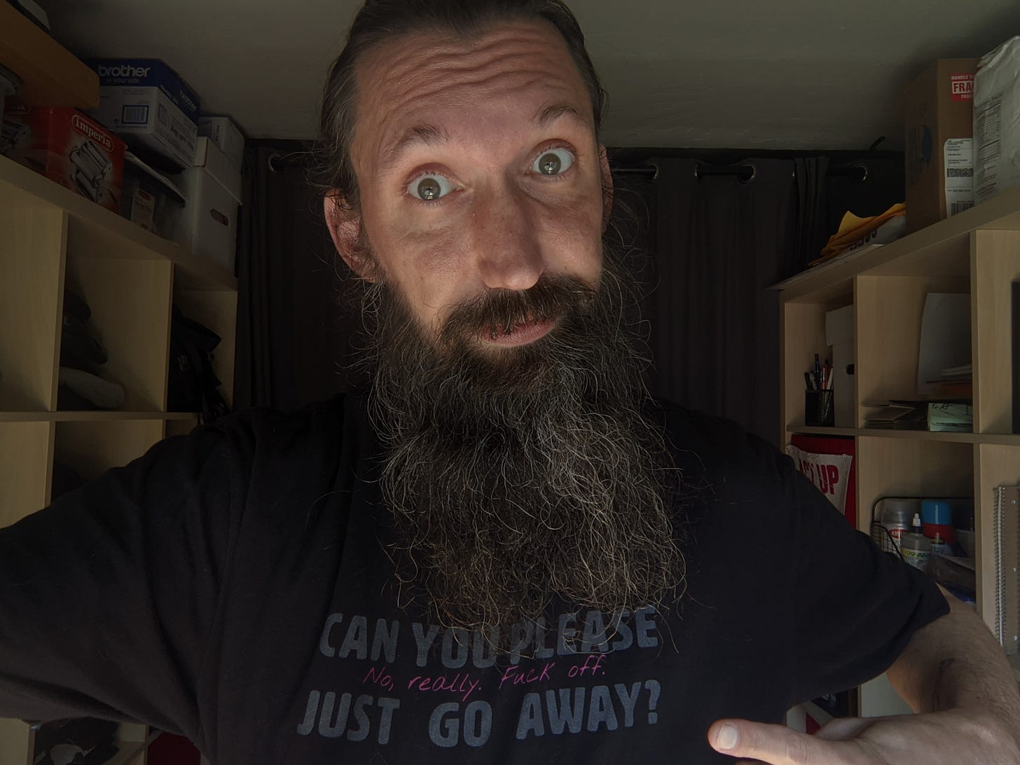 """A selfie of Jason wearing a black t-shirt with the words, """"Can you please just go away? No, really. Fuck off,"""" written on it. They are against a backdrop of bookshelves filled with art supplies. The expression on Jason's face fits the saying."""