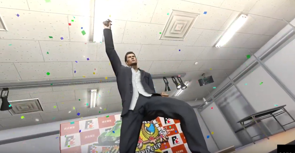 Kiryu, wearing a suit, triumphantly cheering and holding a tiny remote controlled car and surrounded by confetti.