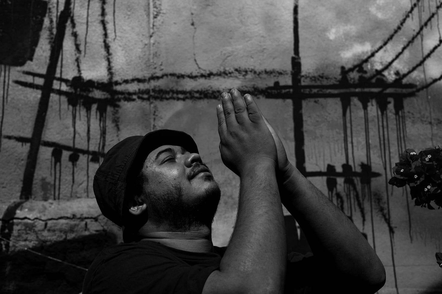 Fotografia em preto e branco mostra Thiago Vinicius com as mãos levantadas para o céu, em prece.
