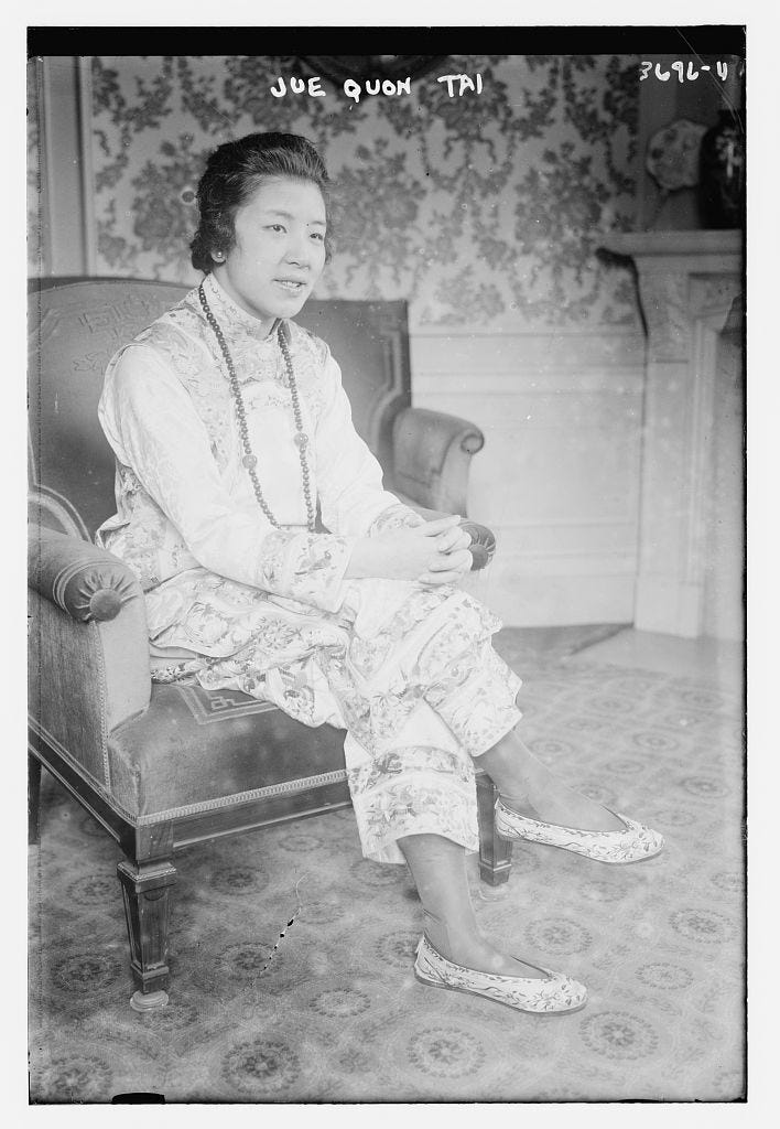 Jue Quon Tai in 1915, she sits in an arm chair in a traditional Chinese silk pantsuit with slippers