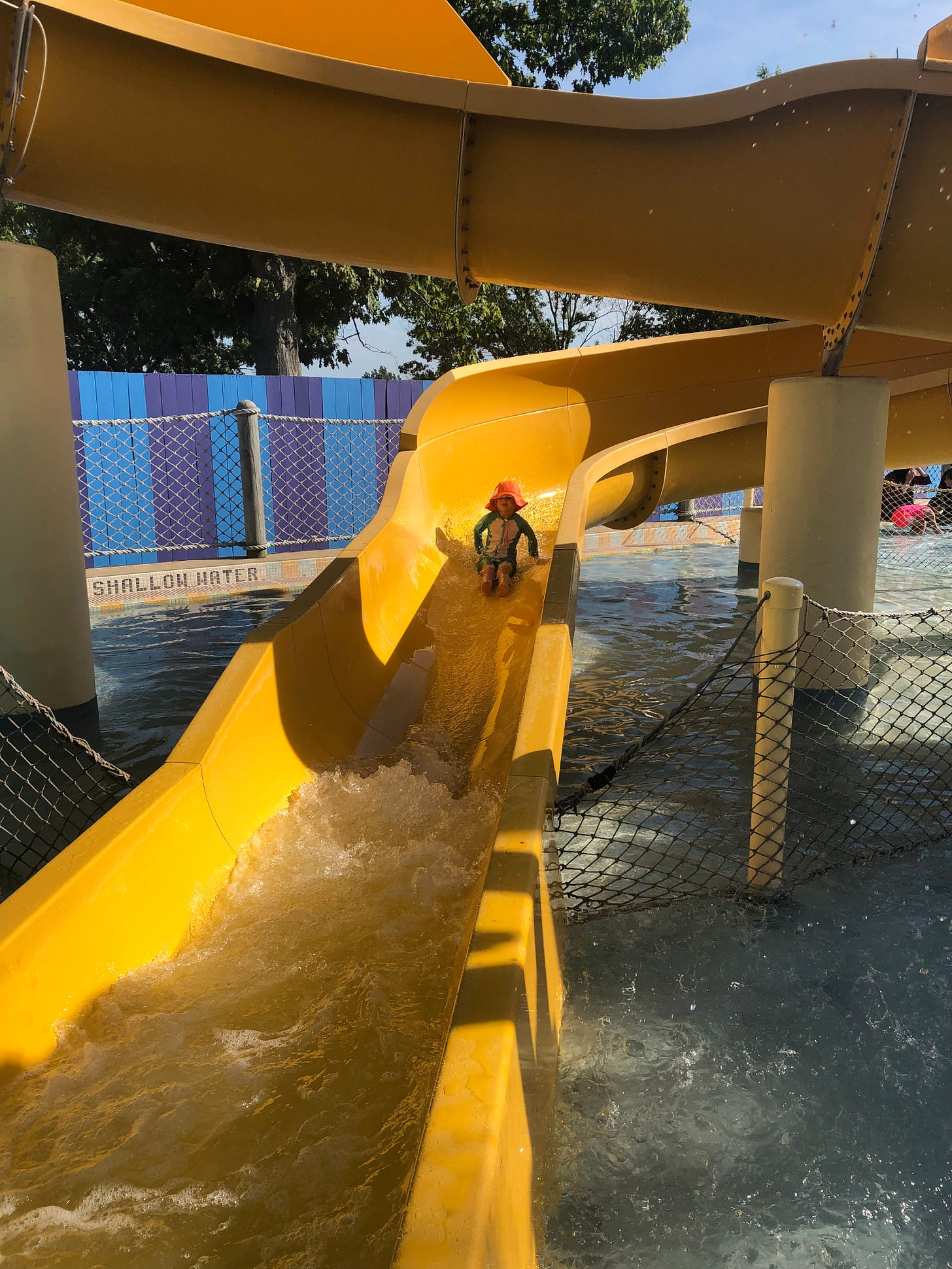 Photo shows a 4 year old in an orange hat on a winding yellow water slide.