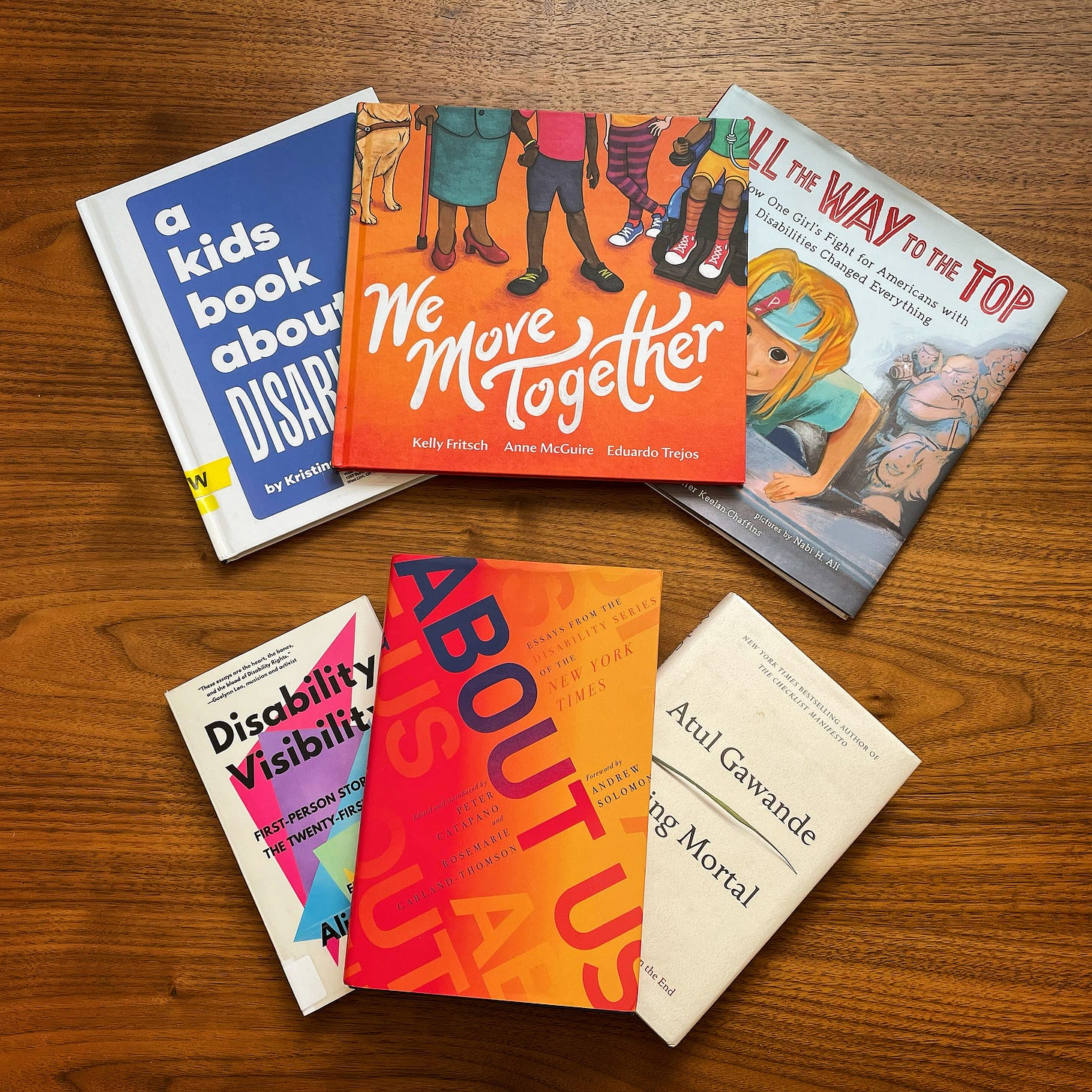 Six books are fanned out on a wood-grain background. On the top are A Kids Book About Disability, We Move Together, and All the Way to the Top. On the bottom is Disability Visibility, About Us and Being Mortal.