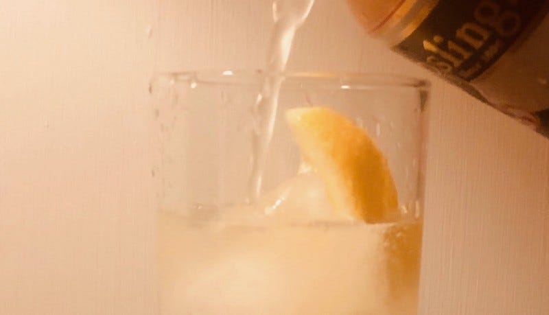 Closeup of a clear liquid being poured into a glass with a lemon wedge in it.