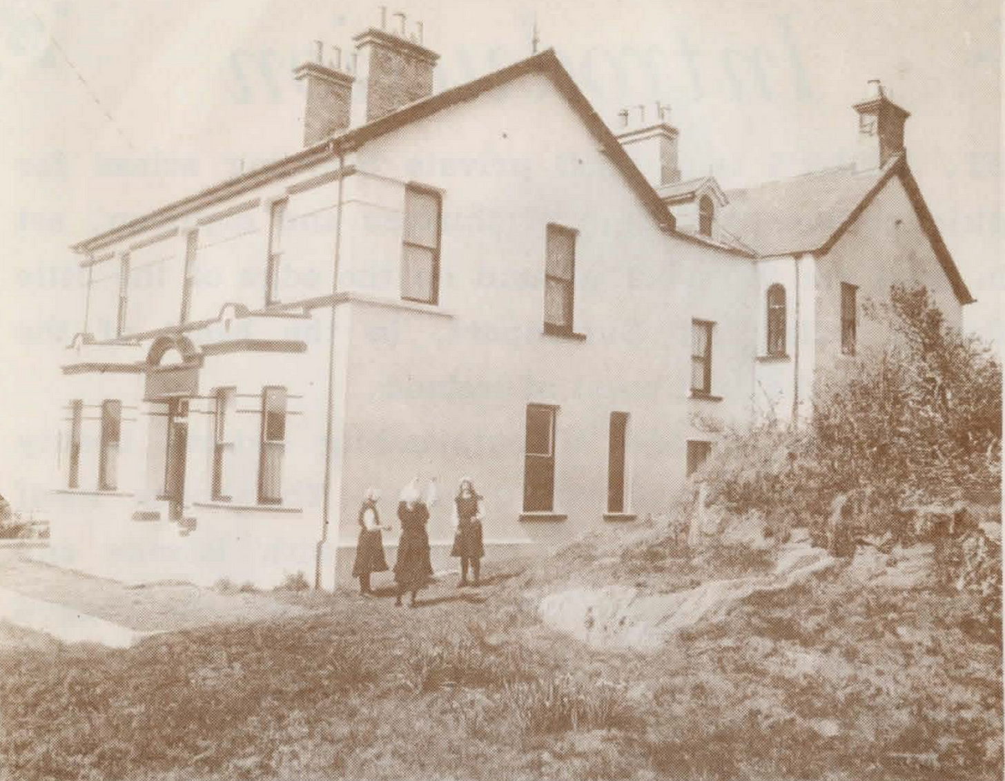 Black and white photograph of a large two-story house, with three women in nineteenth century schoolgirl garb playing out front.
