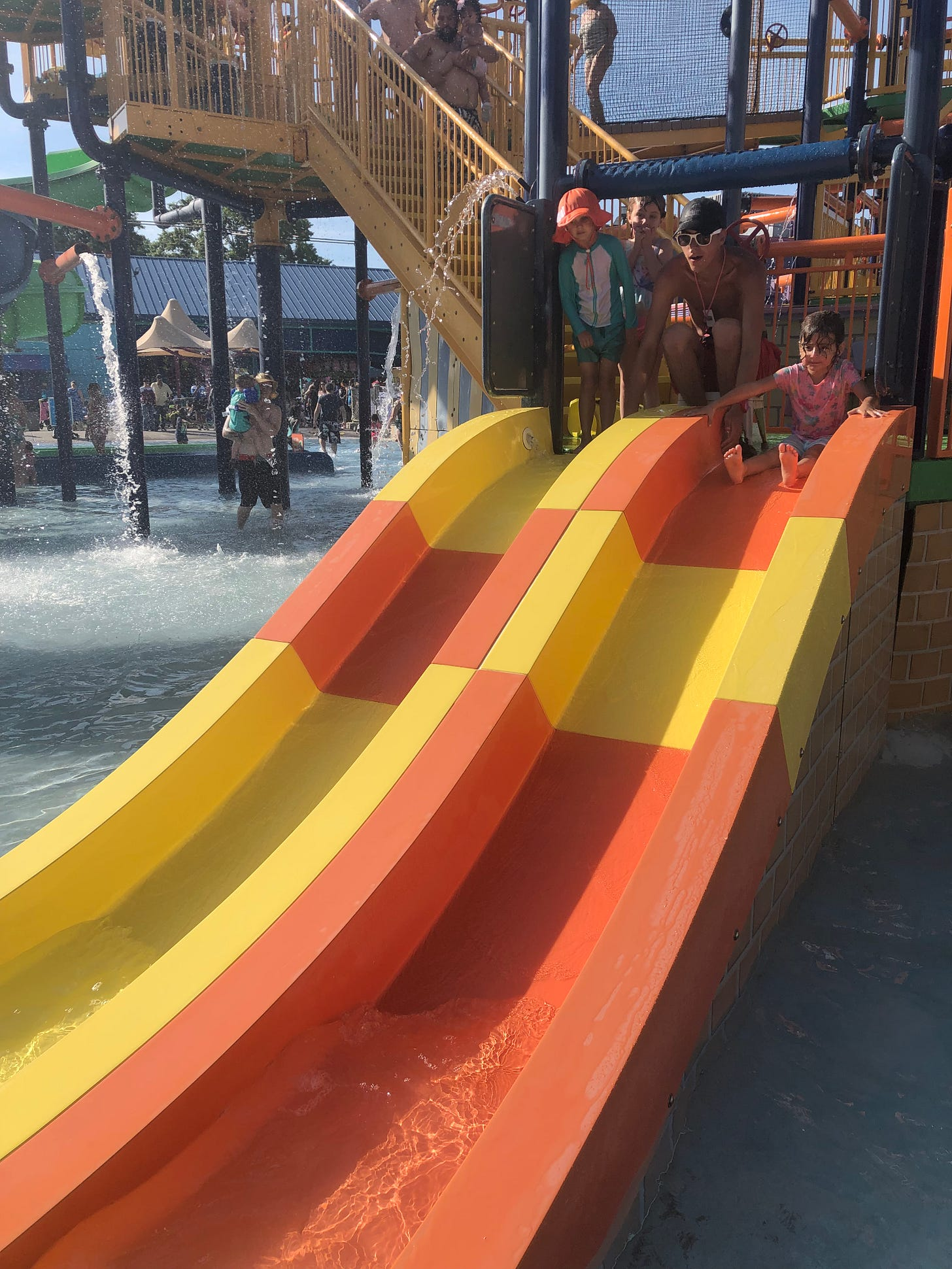 Photo shows a climbing structure with a small side-by-side water slide with two kids and a lifeguard.