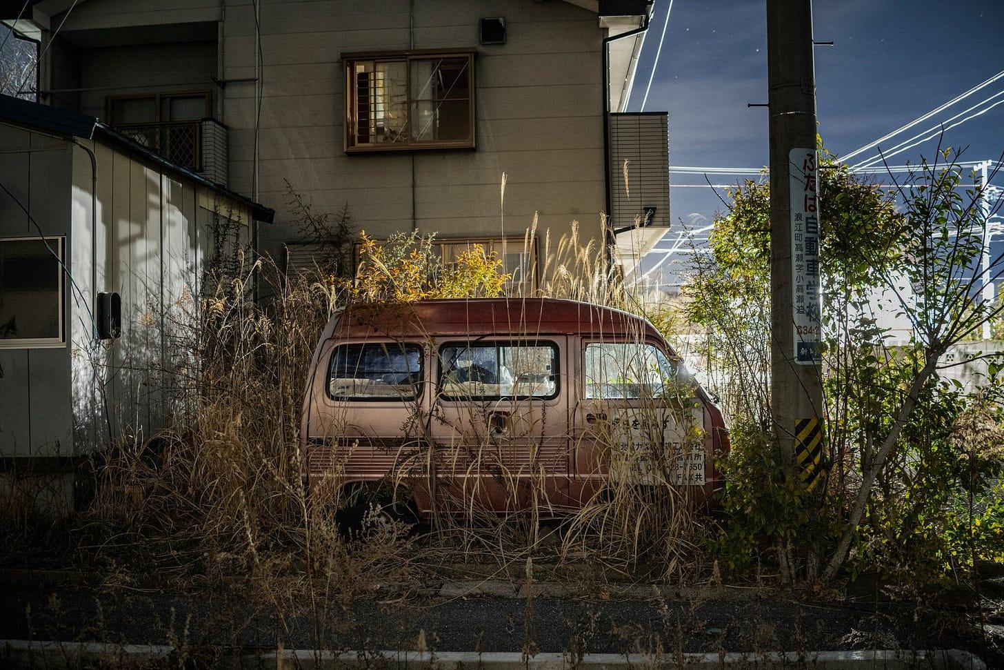 Photo of an overgrown abandoned minivan in Fukushima Japan.