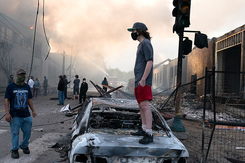 File:A man stands on a burned out car on Thursday morning as fires burn behind him in the Lake St area of Minneapolis, Minnesota (49945886467).jpg