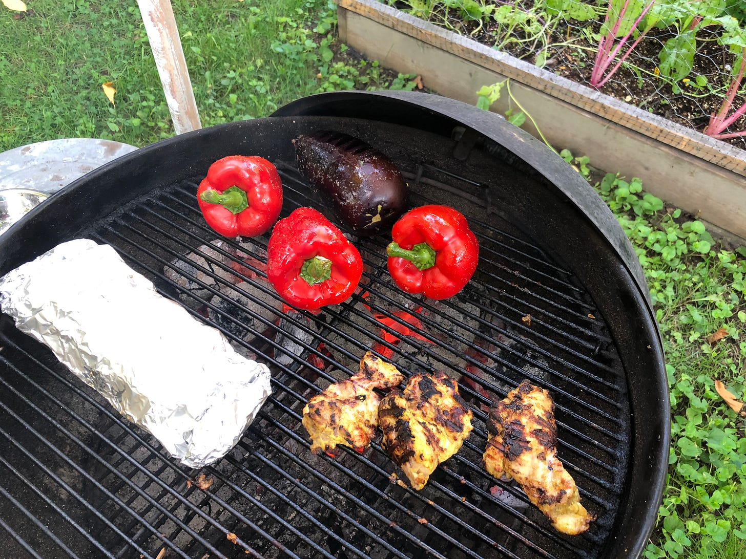 A charcoal grill with XYLO charcoal blocks burning. Three red peppers and an eggplant are directly over the coals. A foil packet of potatoes and some marinated chicken thighs are offset slightly and not directly over the coals.