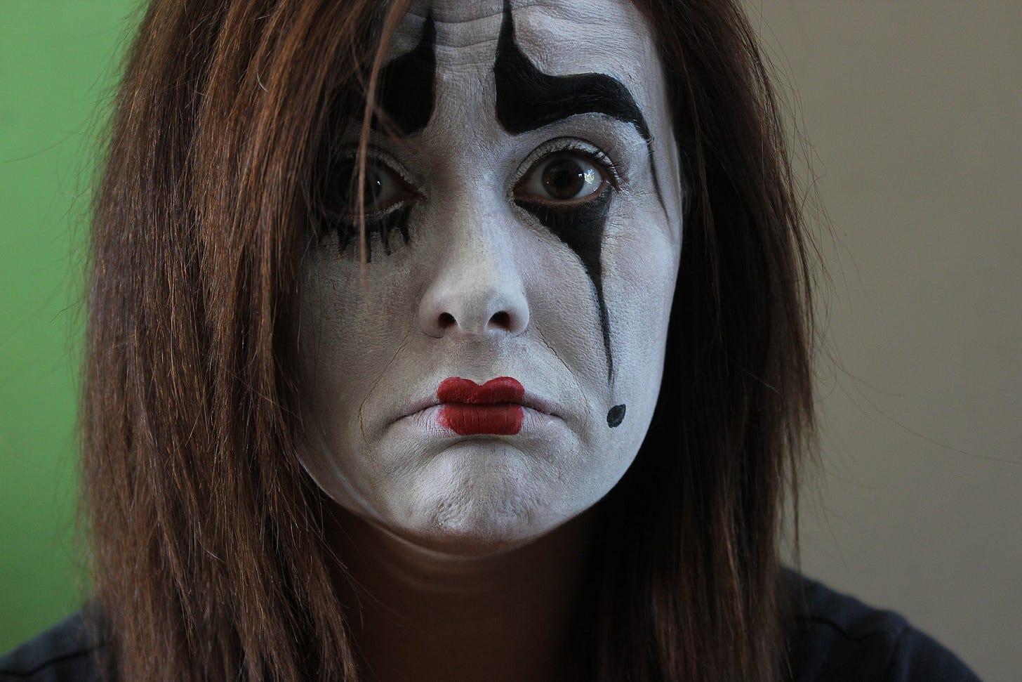 a sad looking female mime artist