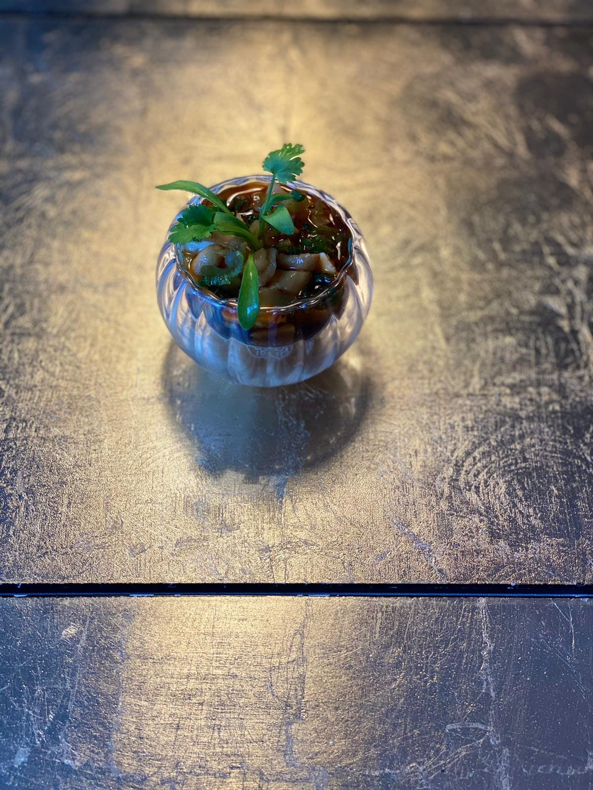 An image of a small round transparent glass container filled with tofu, sauce peanuts and topped with herbs set on a stainless steel surface