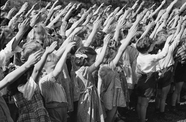 Several dozen young elementary-age children raise their arms toward a flag in an outdoor setting