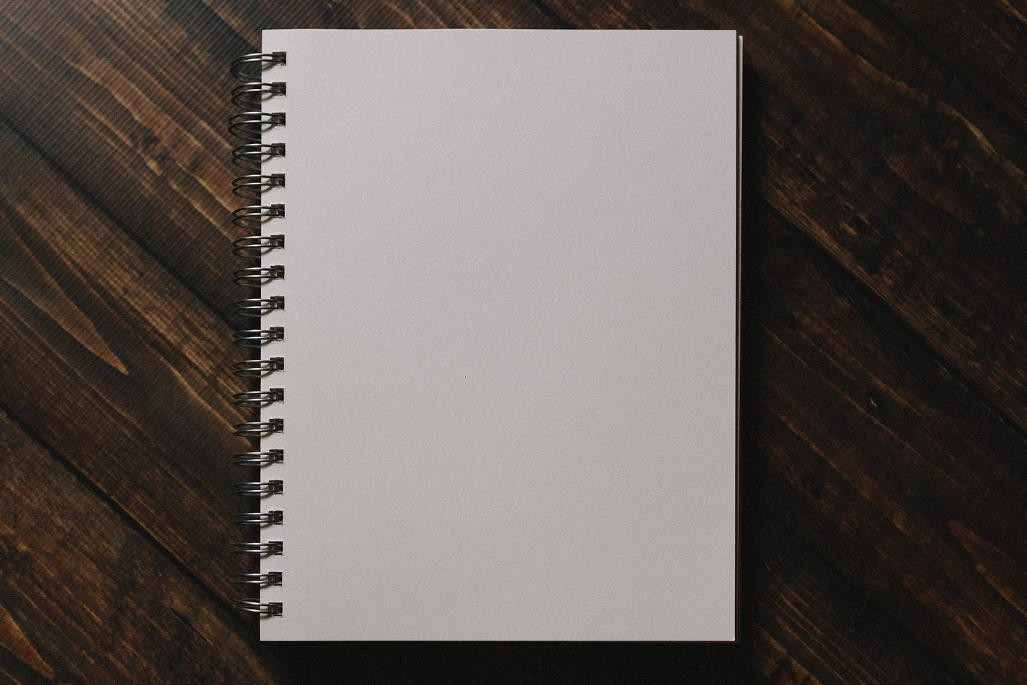 White notebook on brown wooden table.