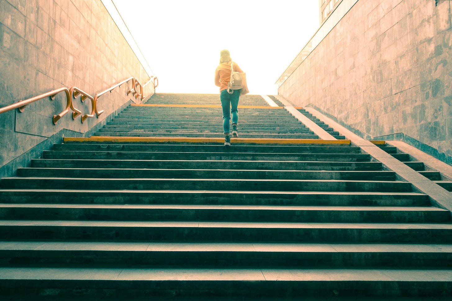 Woman climbing steps towards the light: Beneath the obvious is a profound principle.
