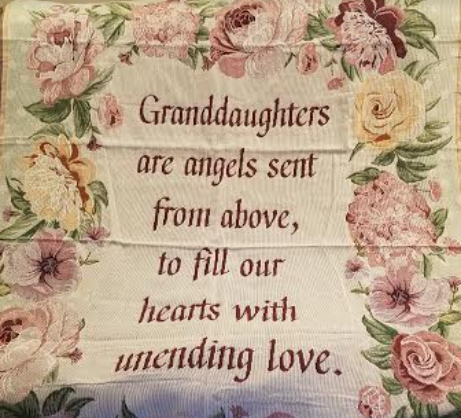"Photo of woven blanket. Primary color is cream and there are cream and white very large flowers around the border. In the center in dark pink words it says, ""Granddaughters are angels sent from above, to fill our hearts with unending love."""