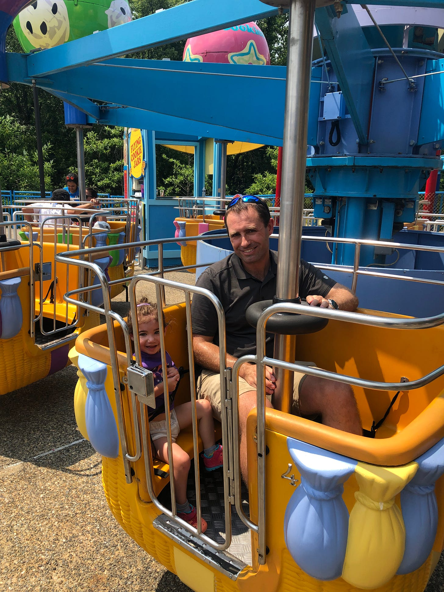 Photograph of Lila and Mark on a ride.  Lila is smiling.