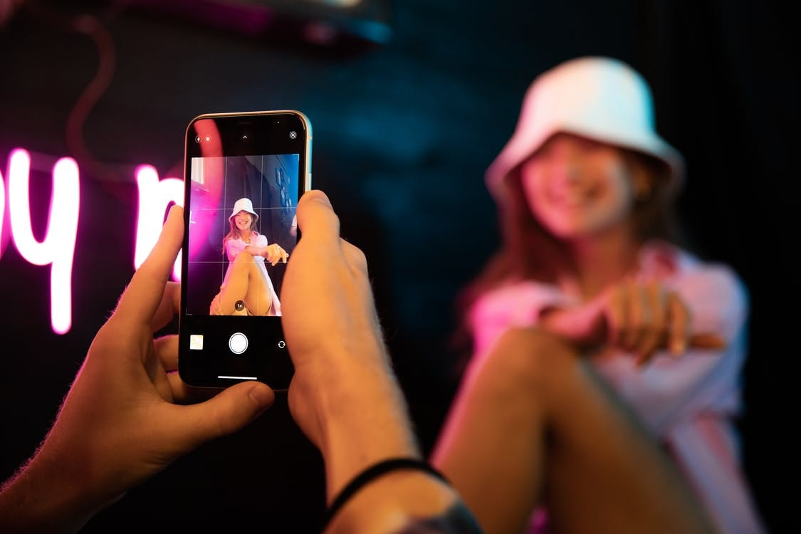 Woman in White Cap Holding Black Iphone 5