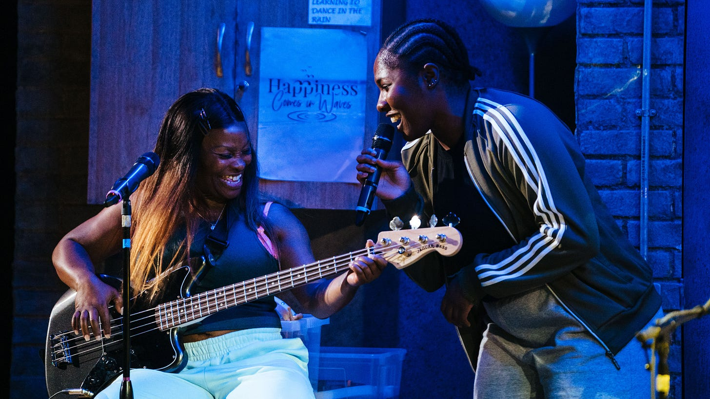 Production image -- Eddy Queens's character plays bass whilst Lara Grace Ilori's character brandishes a microphone.
