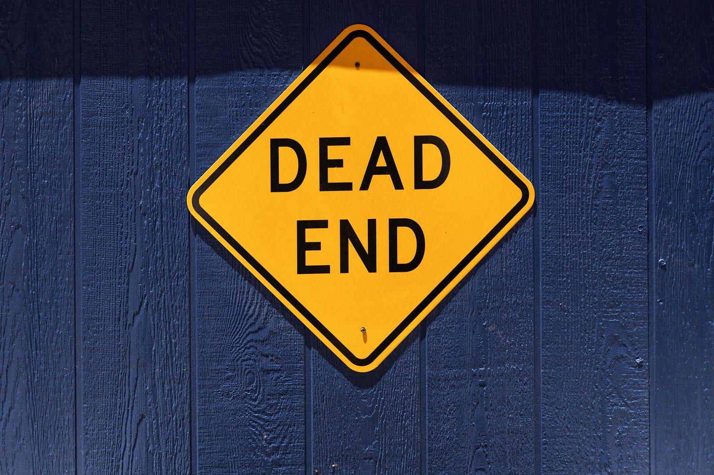 """Image of a yellow sign that says """"ead end"""" mounted on a blue wall, for article by Larry G. Maguire"""