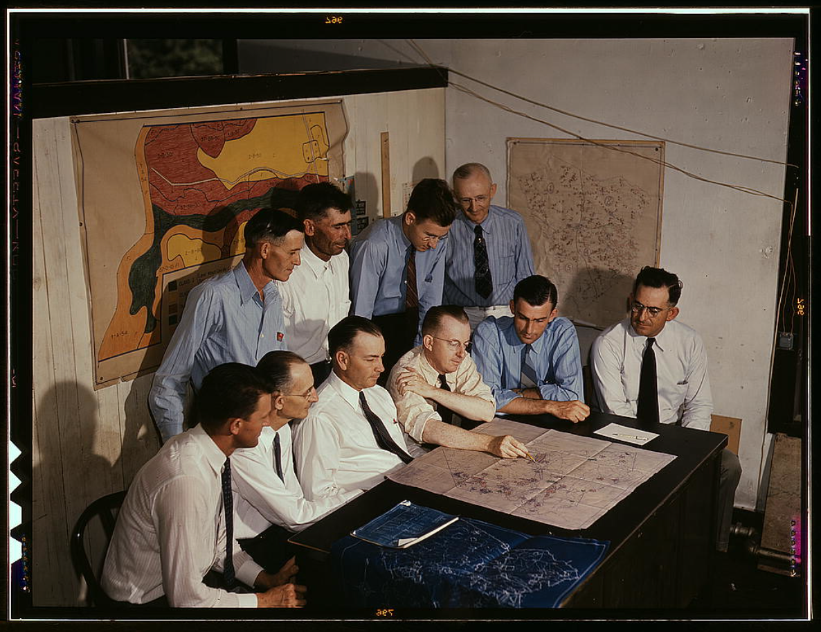 a bunch of white men in ties around a table, likely mid century