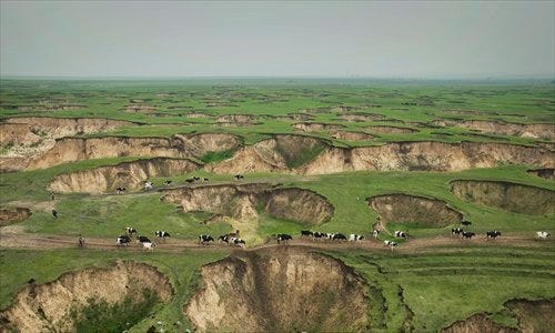 Grassland at a coal mine in Baorixile, Inner Mongolia, is dotted with pits left by ruthless exploration over the past few decades. Photo: Lu Guang, courtesy of Greenpeace