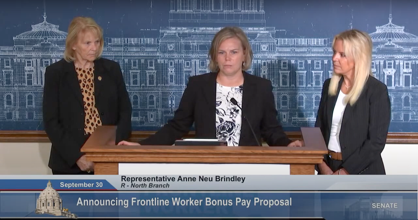 Three blonde white women wearing black blazers stand behind the podium with stern faces