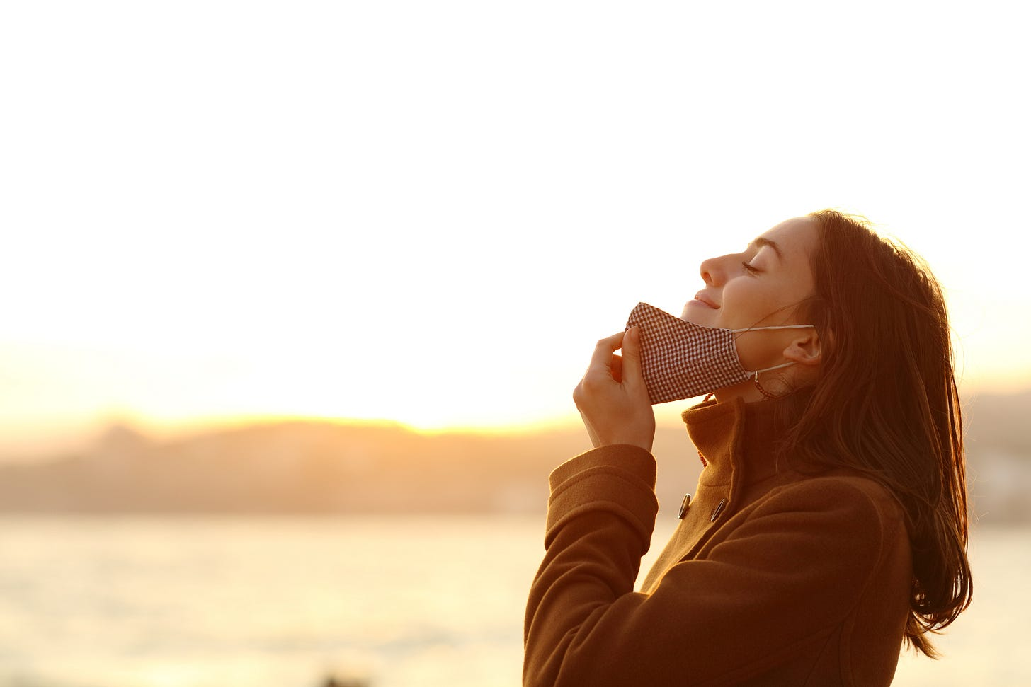 Woman pulling down mask and smiling at the fresh air