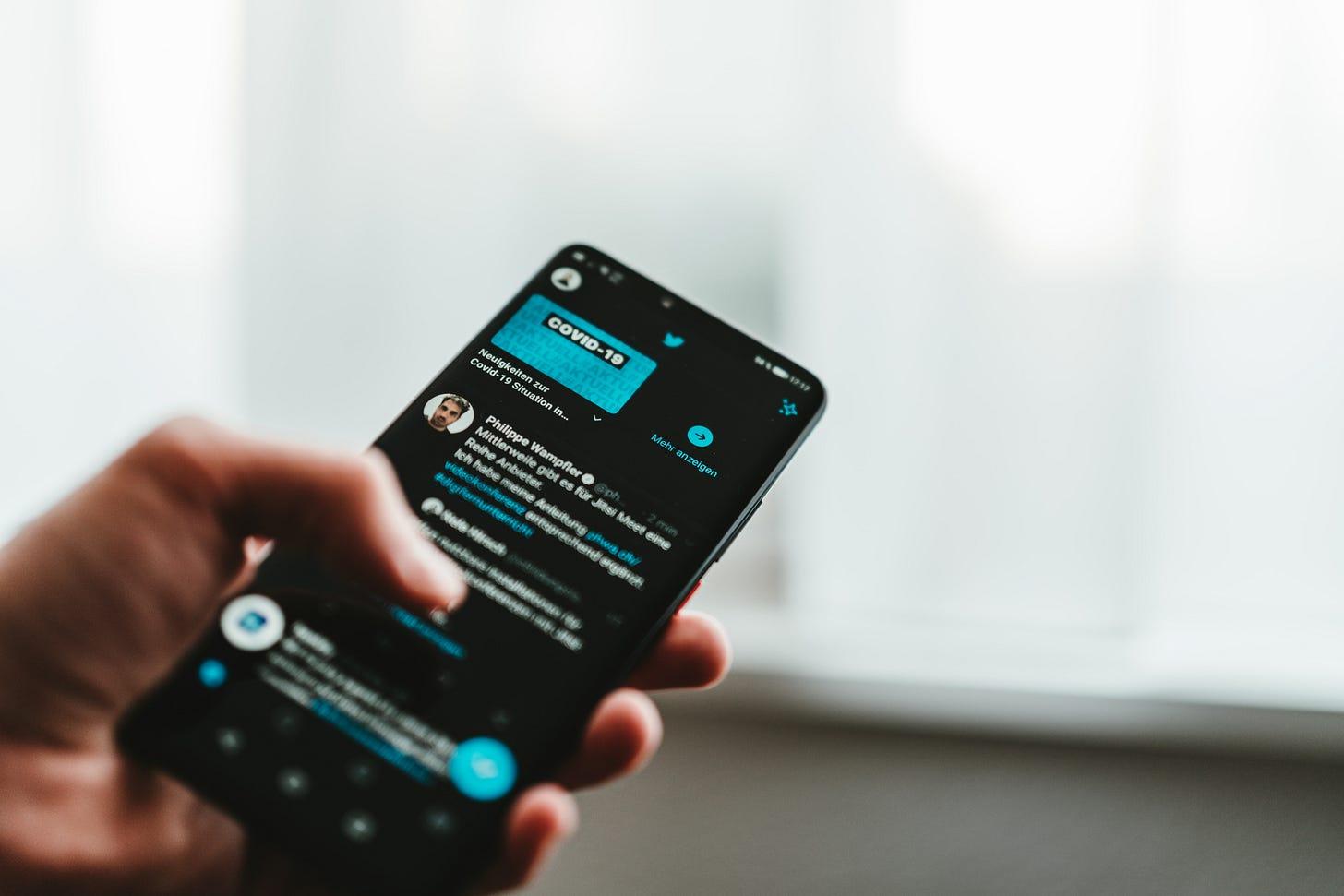 Twitter shown on a phone. (Claudio Schwarz / Unsplash)