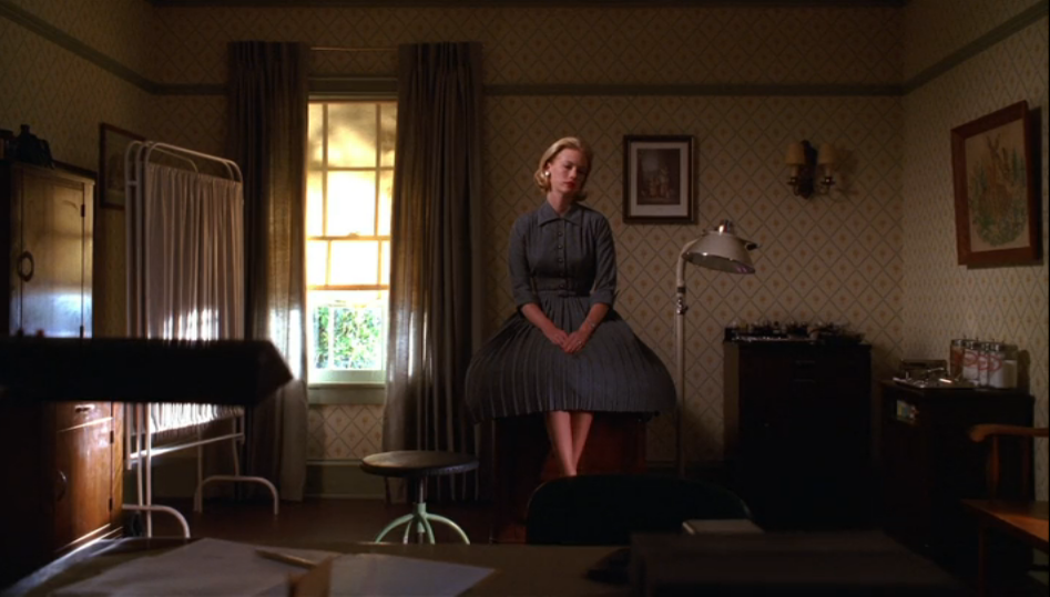 Betty Draper waits in her doctor's office in a gray dress on Mad Men Season 2 Episode 13, Meditations in an Emergency