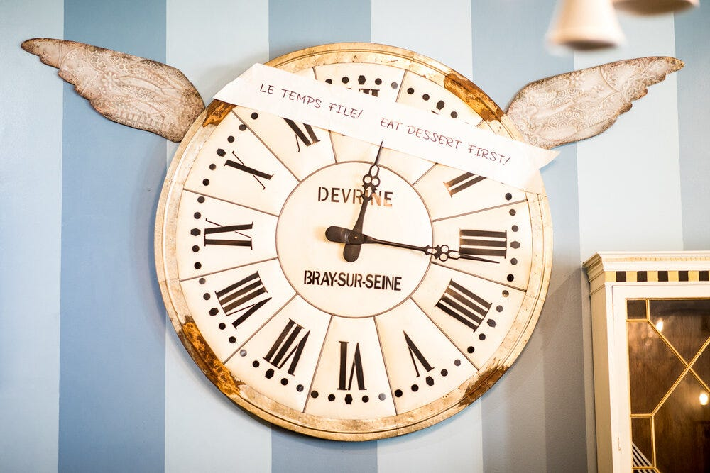 A large clock inside Amélie's Bakery.