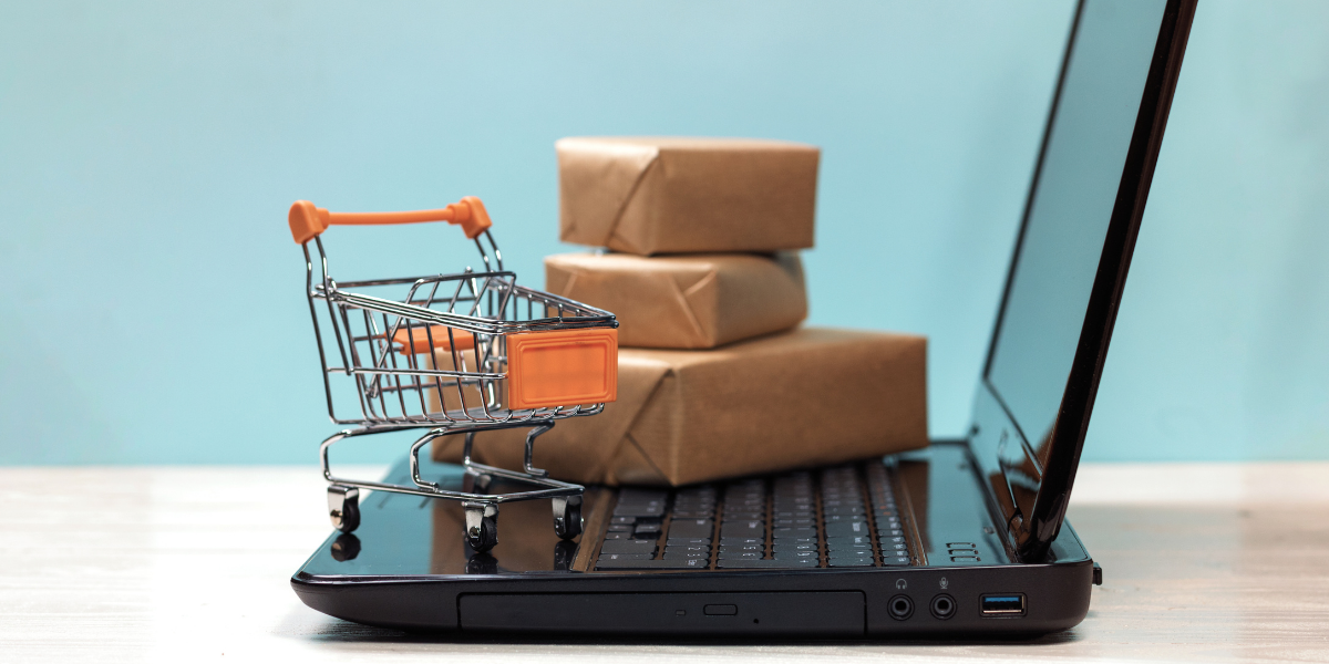 Mini shopping cart and packages on top of a laptop (an illustration).