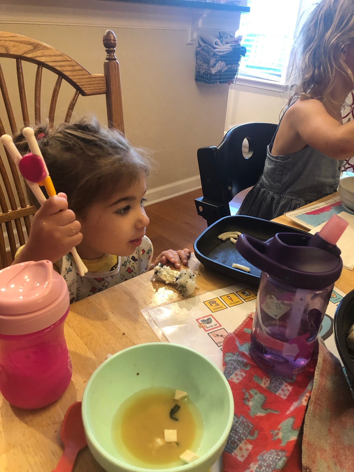 photo of a toddler holding a pair of chopsticks sitting at the dining table
