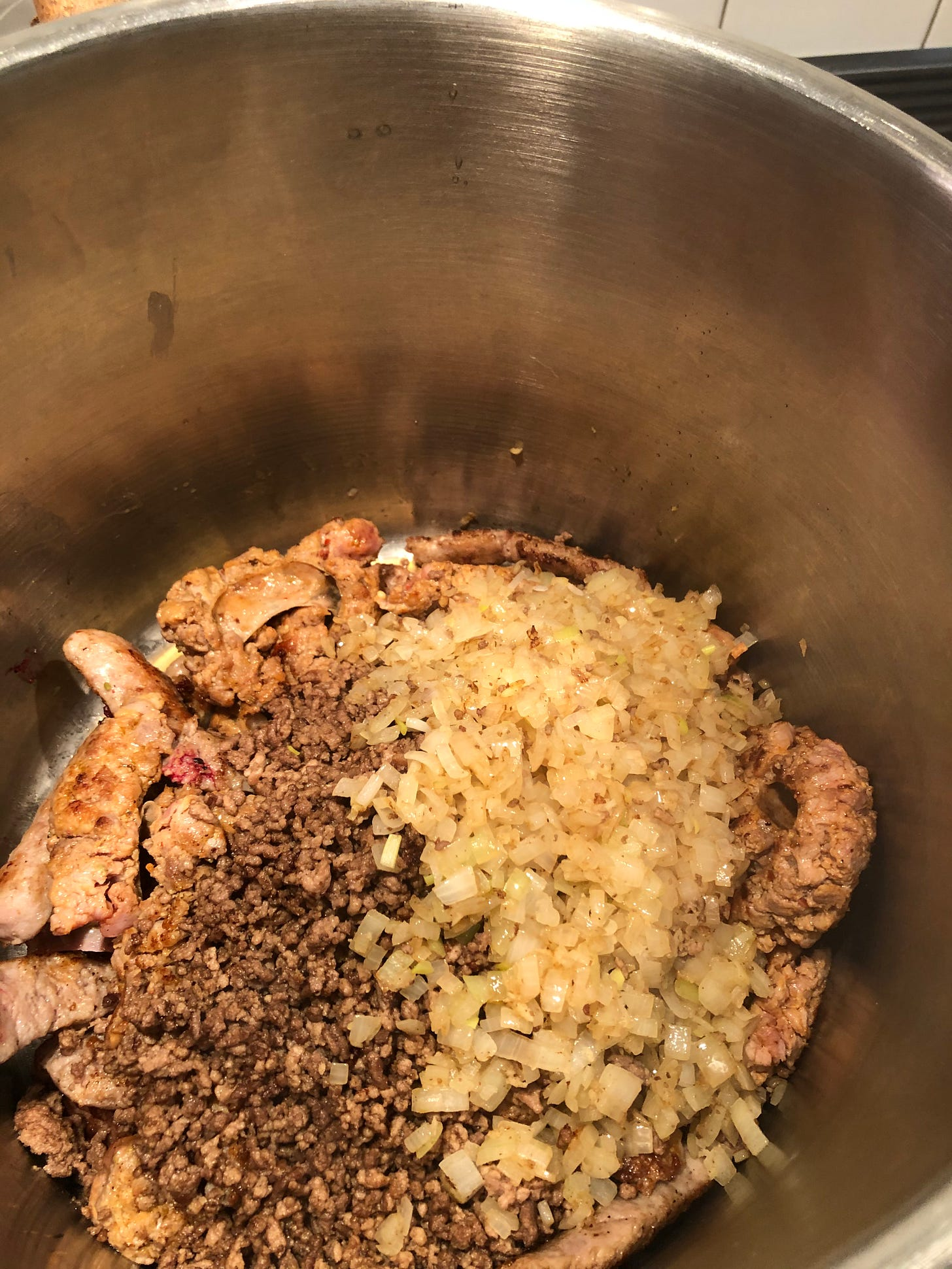 The meats previously shown, now browned with some sauteed onions in a large stock pot