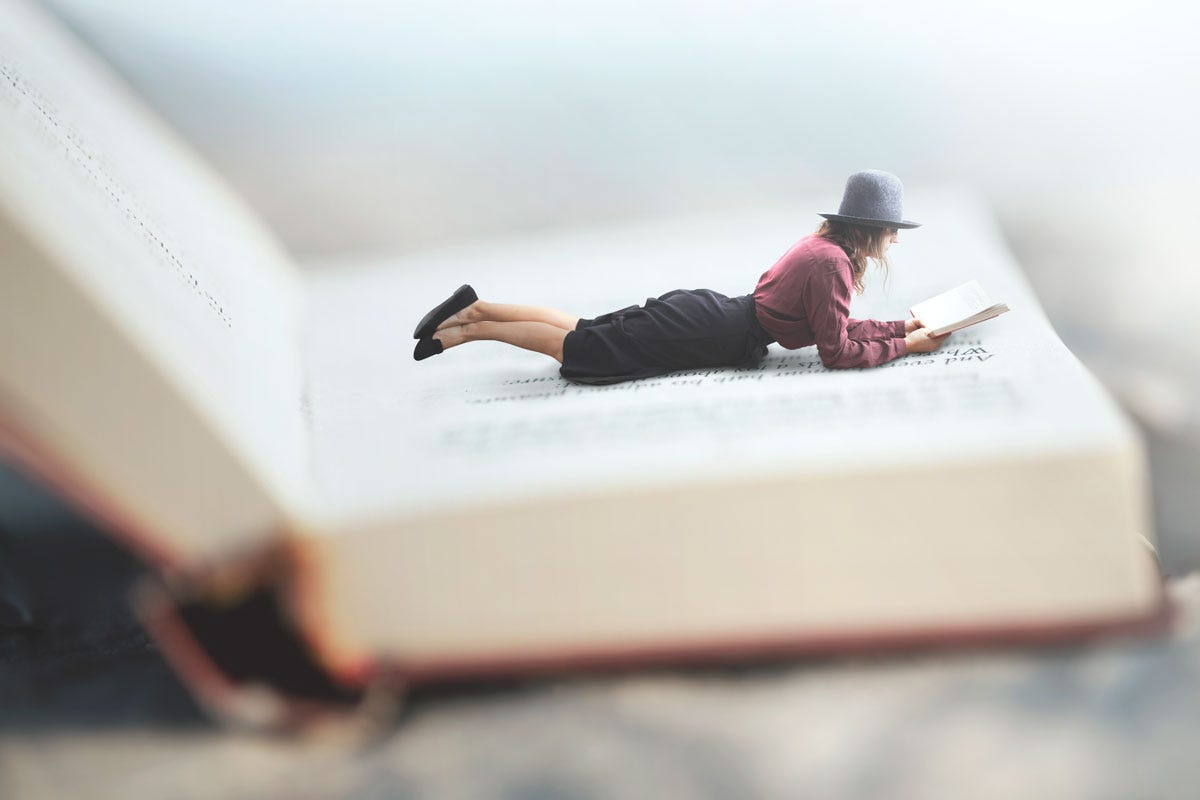 Woman Reading Book While Lying on Giant Book