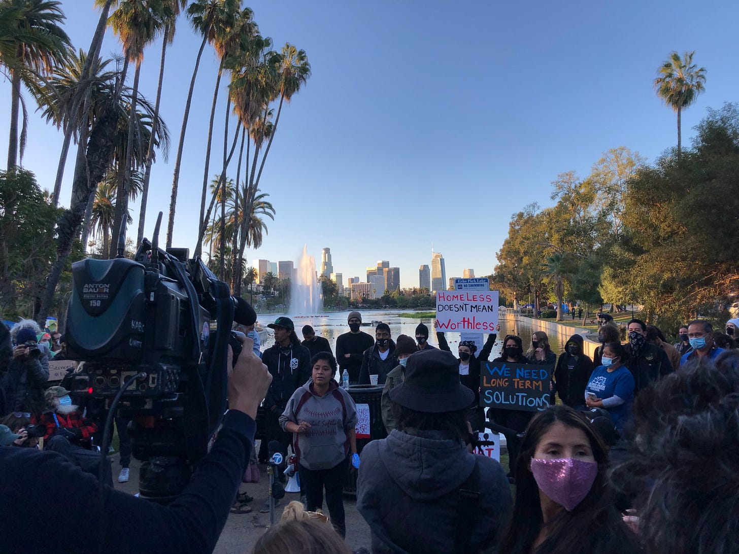 News cameras videotape a crowd of people holding a press conference. Palm trees and skyscrapers in the background.