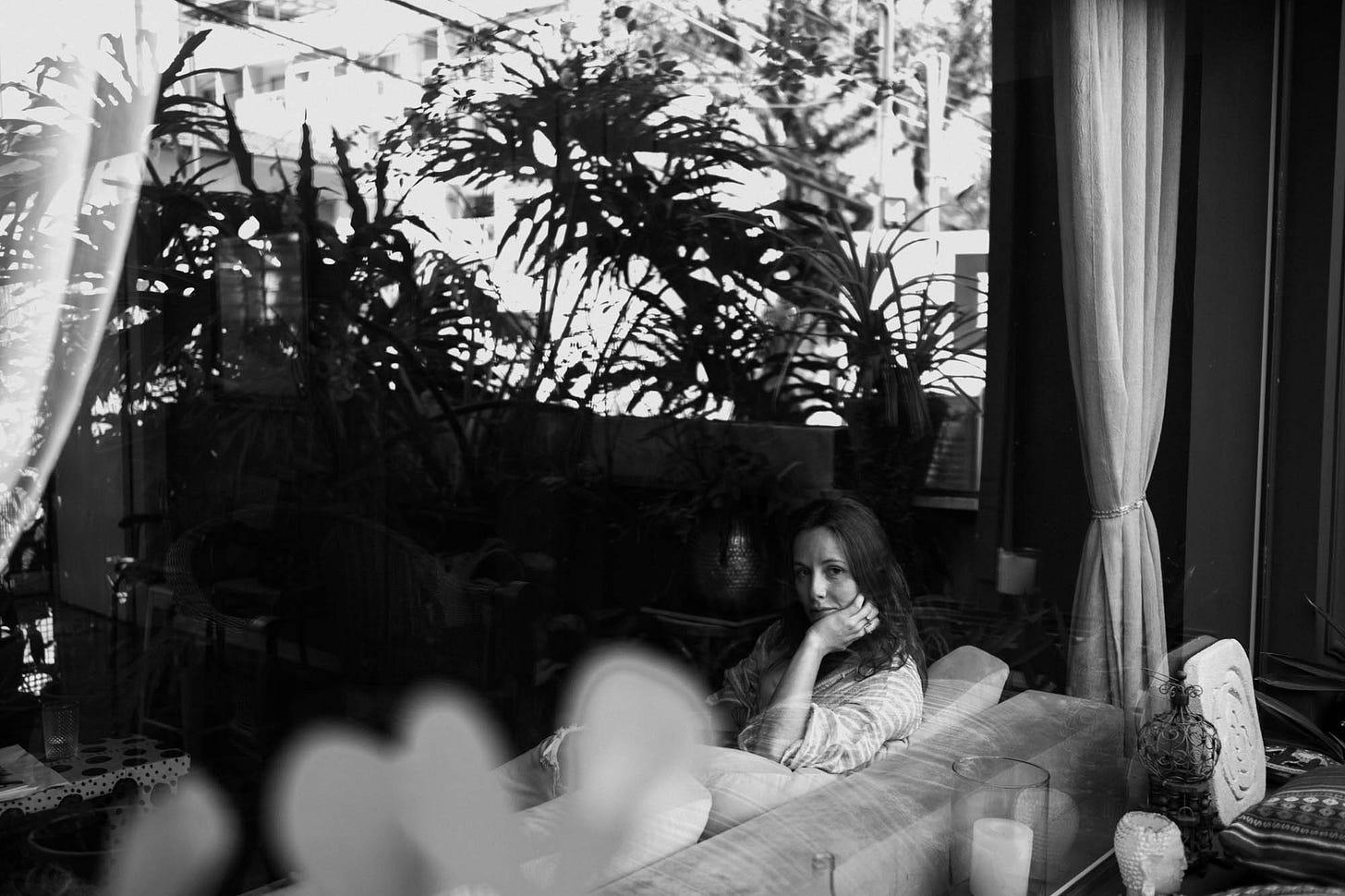 Mulher sentada em sofá atrás de vidraça olhando pela janela através de plantas, imagem em preto e branco