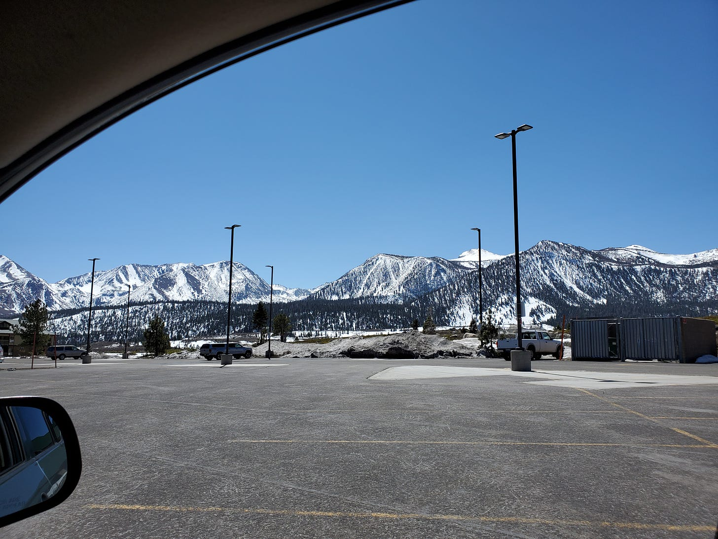 Image of snow bedecked Sherwin Mountains in background, an empty park lot in the foreground.