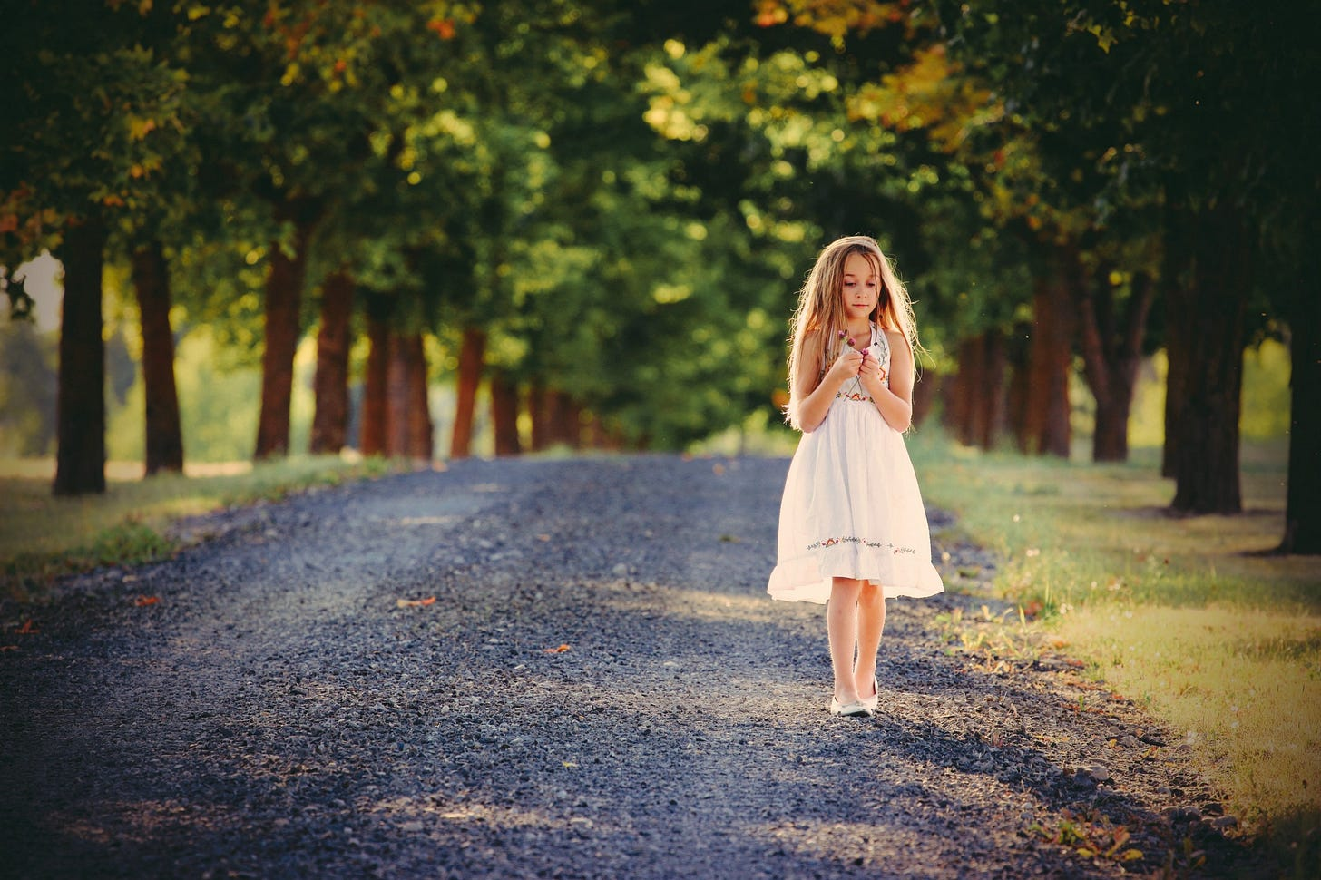 Young girl walking down a country road wearing a dress.