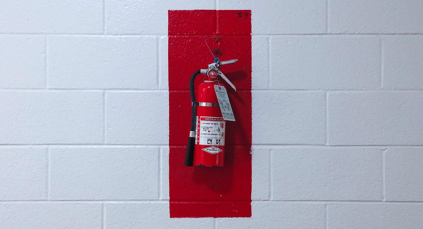 fire extinguisher on white cinder blocks