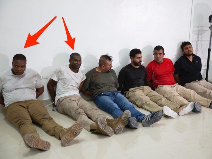 Six men accused of killing the Haitian president sitting on the floor. Two arrows point out American citizens James Solages and Joseph Vincent