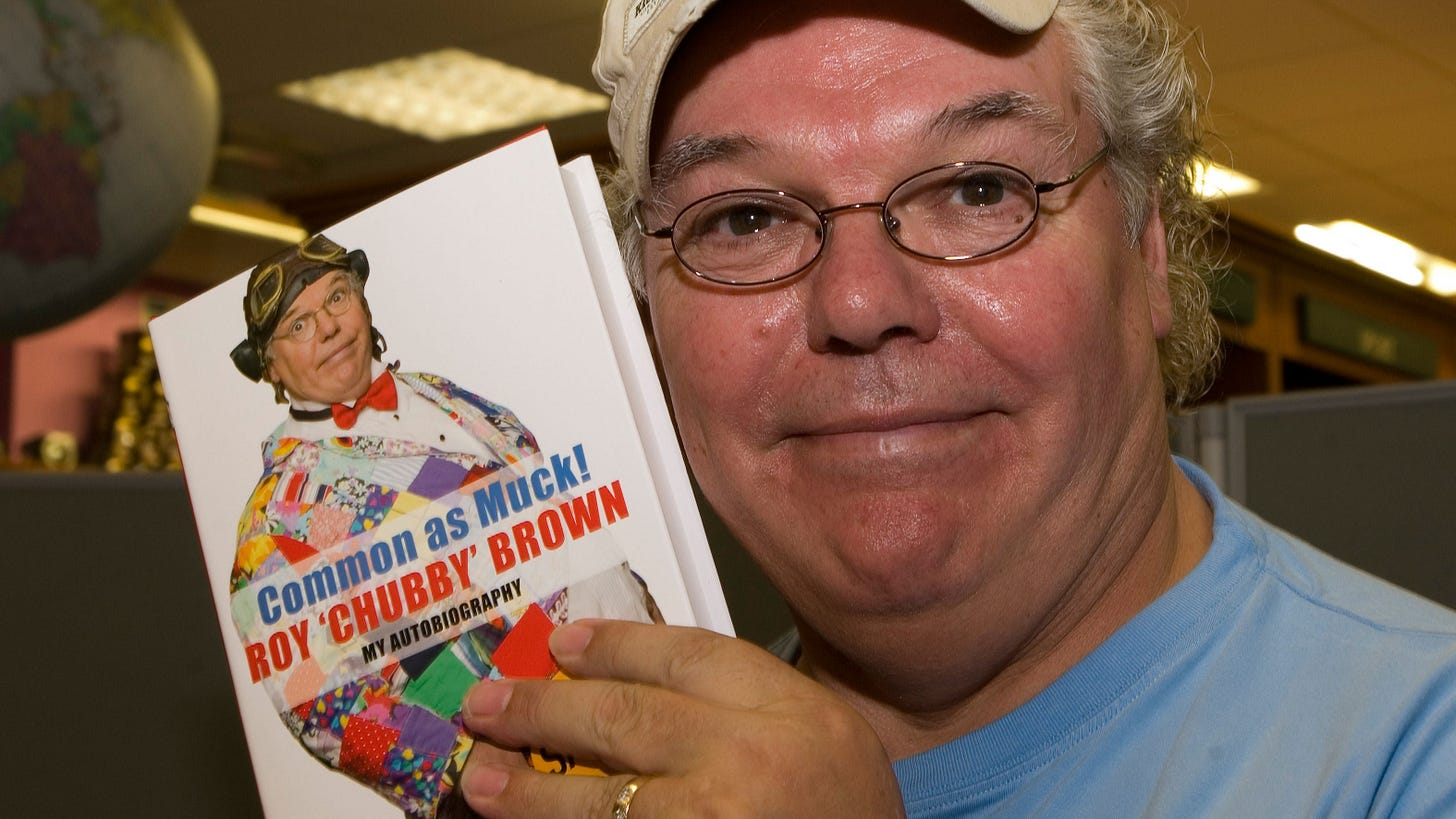 Comedian Roy 'Chubby' Brown holds up a copy of his autobiography Common As Muck.