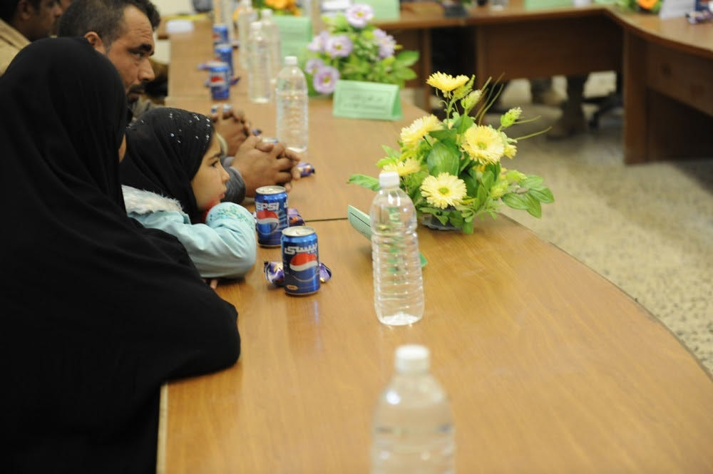 A child, together with her mother, sit at a table. There are flowers, water bottles, cans of Pepsi, and individually wrapped snacks on the table. The mother and daughter are there to recieve condolence pay.